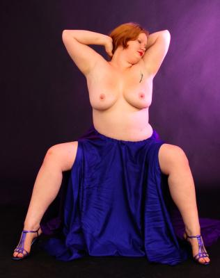 Swan Song posing topless in blue skirt and purple strapped shoes.