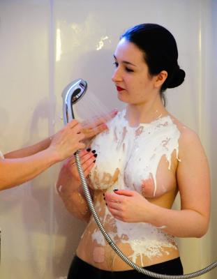 Jess covered in cream icing while Lady J washes it off.