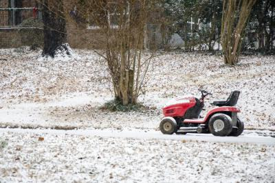 Abandoned lawn mower in the snow.