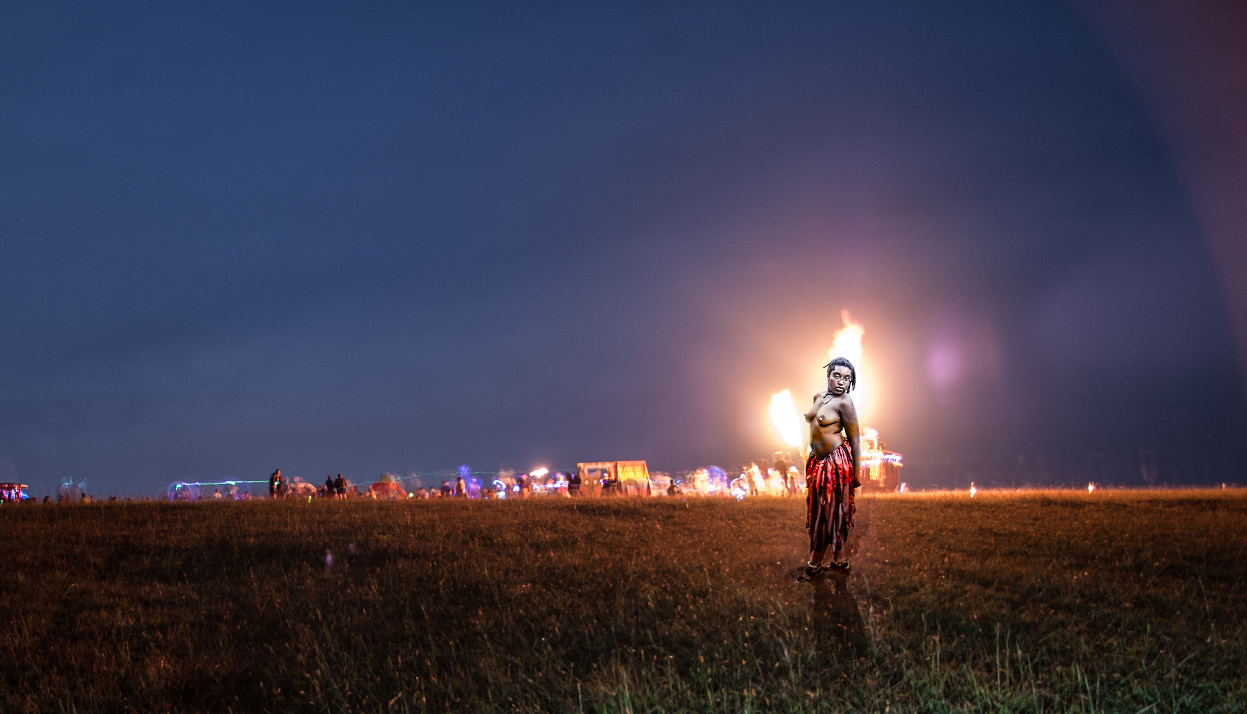 The beautiful and vibrant Nikki standing before a fire-art display at a regional Burn. This is a composite of two photos from two different burns.